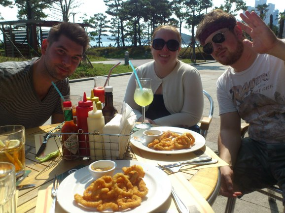 Adam, Heather and Andrew sat in the sunshine outside Geckos, with their amazing calamari. Haeundae, Busan.